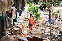 A woman walks through a camp in Mumbai that has been setup to receive environmental migrants who have fled drought-affected regions in the state of Maharashtra. Living in squalid conditions, the migrants are supplied with basic amounts of water with most working in the city as day labourers to make ends meet for themselves and their families.