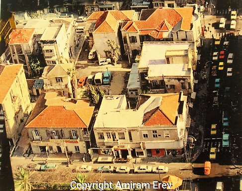 Early Tel-Aviv buildings, the Achuzat Bayit neighbourhood, taken from an aerial perspective, shows roof tops and cars parked in the street.