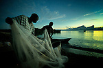 Two men prepare their fishing nets before dawn in Karonga, a town in northern Malawi. Fish from Lake Malawi, which is bordered by Malawi, Tanzania and Mozambique, provide an important part of people's diet in this area.