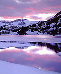 USA; California; Sierra Nevada Mountains.; Snow covered mountians reflecting in Ellery Lake at Sunset