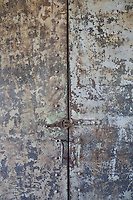 A detail of a metal cupboard with a distressed finish with simple lock and handle