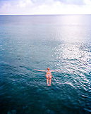 HONDURAS, Roatan, woman floating on sea surface