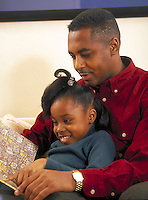 African-American father reading to daughter.