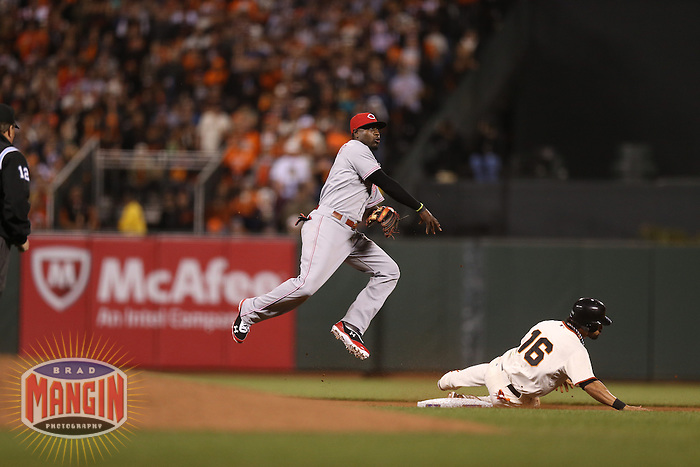 SAN FRANCISCO - OCTOBER 6:  Brandon Phillips of the Cincinnati Reds turns a double play at second base during Game 1 of the NLDS against the San Francisco Giants at AT&T Park on October 6, 2012 in San Francisco, California. (Photo by Brad Mangin)