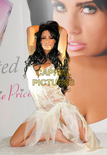 "KATIE PRICE aka JORDAN.photocall to launch her new perfume ""Besotted"" at The Paper Club, Cafe Royal, Regent Street London, England 24th September 2008 .fragrance full length white lace lingerie sheer kneeling bra  black hair extensions hands on head .CAP/CAN.©Can Nguyen/Capital Pictures"