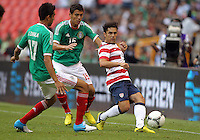 MEXICO CITY, MEXICO - AUGUST 15, 2012:  Herculez Gomez (9) of the USA MNT makes a pass in front of Jesus Zavala (17) and Hector Moreno (15) of  Mexico during an international friendly match at Azteca Stadium, in Mexico City, Mexico on August 15. USA won 1-0.