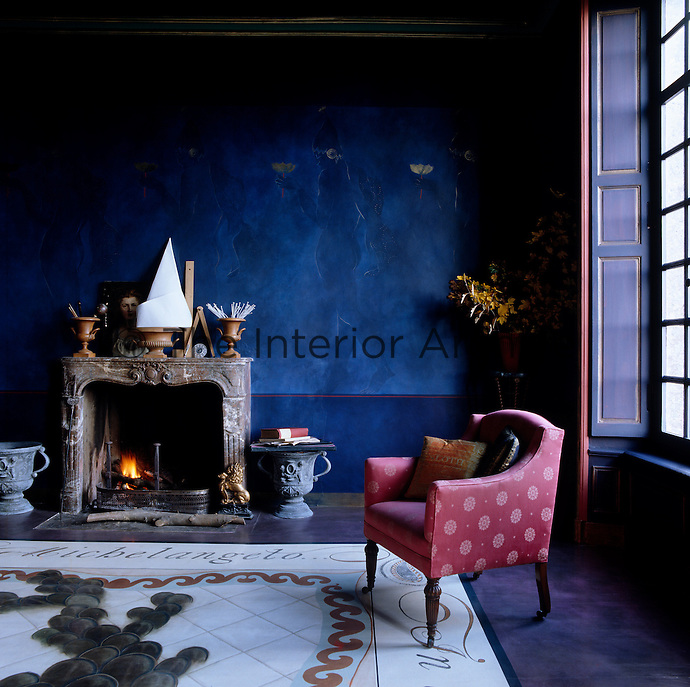 A mural painted in tones of deep ultramarine creates a dramatic and sumptuous atmosphere in this living room