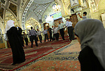 Damascus, Syria. Shiite men praying in Sayyidah Ruqayya Mosque, a shrine located in Damascus, containing the grave of Ruqayyah, the infant daughter of the martyr Hussein of Kerbala. The mosque was built in 1985 by the Iranians in a modern Persian style, Ruqayya being a Shiite saint.