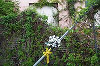 Voghera 16-04-2012:  una croce con dei fiori fuori dalla fabbrica ex Fibronit..L'azienda ha lavorato amianto dal 1914 al 1994 a Broni (PV) causando, in proporzione per numero di abitanti, più vittime per mesotelioma pleurico di Casale Moferrato.