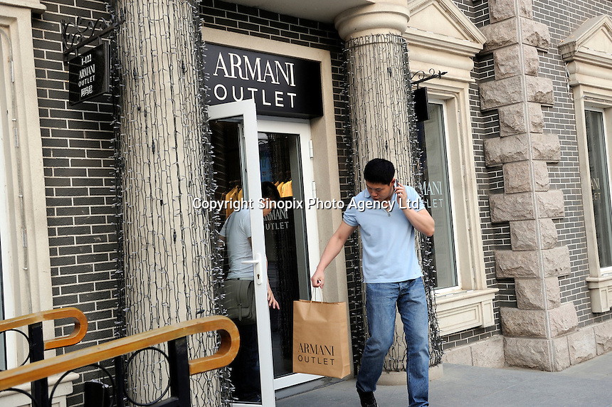 Two Chinese me leave ARMANI outlet store at Beijing Scitech Premium Outlet Mall in Beijing, China. Opened in July 2009, Beijing Scitech Premium Outlet Mall is located in Beijing's most prestigious villa neighborhood. The outlet, featuring Colonial and Victorian architecture, the first of its kind in China, contains gallery of top-tier luxury brands, as well as showcases a wide selection of popular sports and leisure brands at discounted prices..15 May 2010