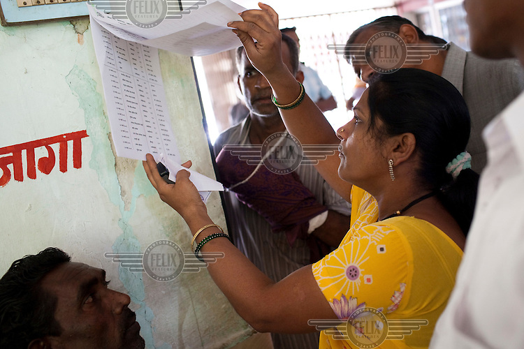 Patients look for their names on a list list as they wait to see doctors at a free clinic for impoverished people. The clinic is organised by the local Rotary Club and some of India's leading micro and plastic surgeons provide treatment.