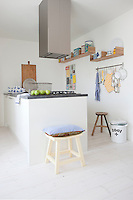 Staggered shelving in the kitchen provides a more playful way of displaying the couple's colourful collection of vintage storage jars and kitchen accessories