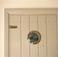 A close up of a contemporary wooden door with a porthole window