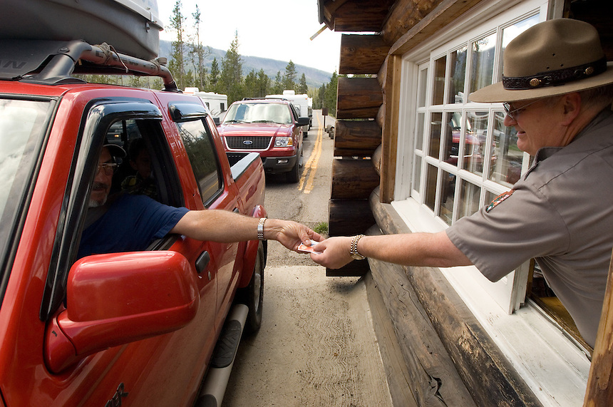 A park ranger takes passes for entrance to Yellowstone National Park Tuesday, May 31, 2005. Yellowstone, the nation's first national park as well as its most popular, attracts millions of visitors each year. Booking lodging in the park is difficult, and confusing online sources can complicate the task. (Kevin Moloney for the New York Times)