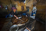 Black Hmong hill tribe woman brewing alcohol in her house, Vietnam