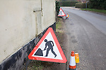 Red triangular sign for men at work  on village street, UK