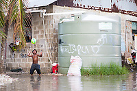 A child plays in floodwaters near a water catchment tank in the Tuvaluan capital of Funafuti. Parts of the island flood at this time of the year due to the 'king tides'. The king tides are seasonal and are characterised by very high water levels in the surrounding ocean. At this time of year the waves inundate the coastline but also water seeps up through the ground which is made of porous coral. This natural phenomenon is particularly serious for Tuvalu, a low-lying atoll island nation, whose highest point is only a few metres above sea level. As sea levels rise, the king tides regularly flood parts of the island and will likely increase in severity in the future, potentially making large parts of the nation uninhabitable. March, 2019.