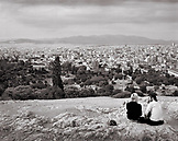 GREECE, Athens, a couple sits on the Rock of Areopagus at the Acropolis and looks out over the city of Athens (B&W)