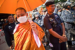 Apr. 12, 2010 - BANGKOK, THAILAND: A Buddhist monk in the Red Shirts and a Thai riot police officer share a shade umbrella in front of the Prime Minister's house on Soi 31 off of Sukhumvit Rd in Bangkok Monday. The funeral cortege for the Red Shirts killed in the violent crackdown Saturday wound through Bangkok and parts of the procession passed by the Prime Minister's home. Thousands of mourners came out to pay respects for dead Red Shirts. 21 people, including 16 Thai civilians were killed when soldiers tried to clear the Red Shirts' encampment in Bangkok. Thousands more came out to call for the government of Thai Prime Minister Abhisit Vejjajiva to step down. Today Gen. Anupong Paojinda, the Chief of Staff of the Thai Army, reiterated that the Army would not use violence to break up the protests and joined the call for the Prime Minister to call new elections. This is the beginning of Songkran, Thai New Year's week, and the government has cancelled the official festivities fearing more violence. It was during last year's Songkan festivities that the Thai Army and police used force to break up the Red Shirt protests. That protest is now called the Songkran Riots.         Photo By Jack Kurtz