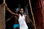 Young men look out from a dwelling in Mabella, an extremely impoverished neighborhood in Freetown, Sierra Leone, Aug. 15, 2012. A decade after the civil war that killed tens of thousands of people and displaced 2 million, Sierra Leone's young people are grappling with illiteracy and unemployment, as well as a lack of basic infrastructure.