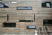 A door virtually disappears in the Padauk cladding which covers the exterior of the house; the slats vary in width and length and are accented at intervals with contrasting slats made of polished stainless steel