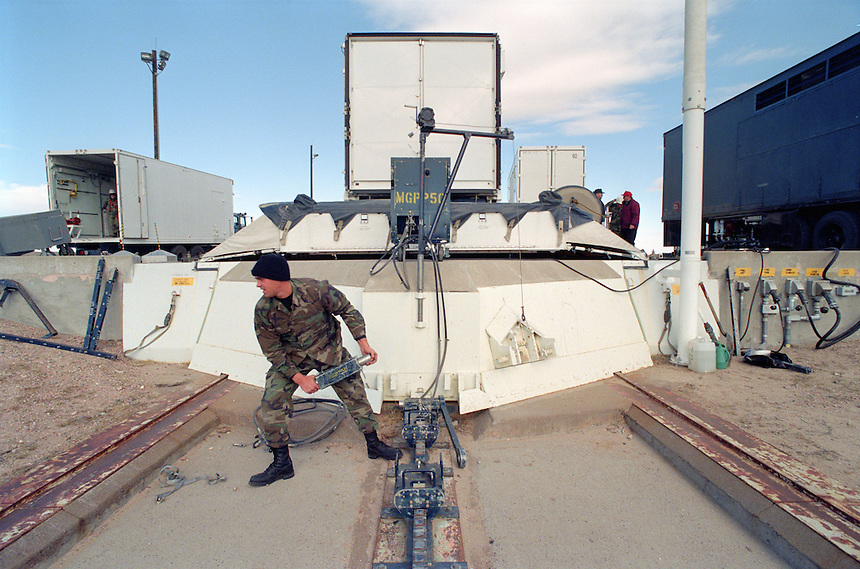 A U.S. Air Force technician attaches a mechanical mule to pull open a four foot-thick blast door covering a Peacekeeper Intercontinental Ballistic Missile silo in eastern Wyoming. A battery was being changed after it's ten-year life had run its course. Intense maintenance schedules are performed on the U.S. missile fleet to keep it in a state of readiness despite the end of the cold war. The 80 foot-tall, 196,000-pound missile fits in a cylinder like a piston, allowing crews to gently raise and lower it with only 30 pounds per square inch of air pressure. The missile was raised a few feet to allow access to bolts.