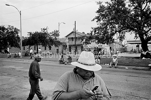 New Orleans, Louisiana.USA.August 1, 2006..Mexican workers wait, on a center city street, for people to drive by and hire them for the day. These workers have been gutting homes and businesses, repairing roofs and cleaning up the city after hurricane Katrina struck nearly a year ago. The levees broke leaving 80% of the city flooded. This labor is important for rebuilding the city but most of the workers are under paid and work long hours.