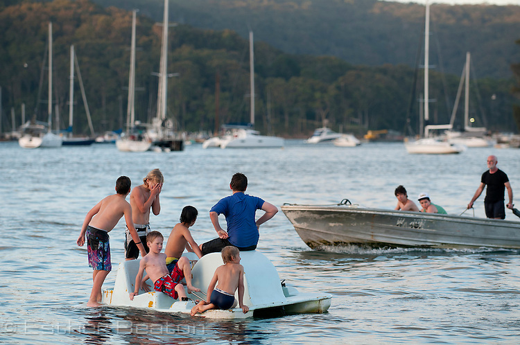 Young boys playing around pedal boat. Christmas Eve dog races from Scotland Island to Church Point, Sydney, New South Wales