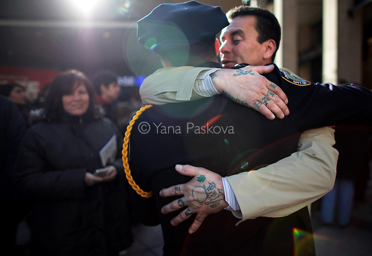 George Lambert hugs his son, police officer Matthew Lambert, 21, after his graduation ceremony at Madison Square Garden in Manhattan, New York on December 29, 2014. Tension against police has recently escalated after the killing of several unarmed black men during routine arrests across the country.