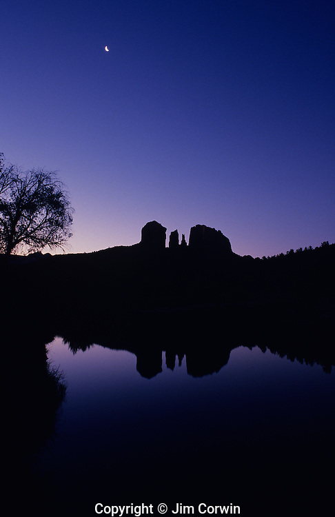 Cathedral Rocks from Oak Creek Canyon Red Rock Crossing with crescent moon over silhouetted rock formations with reflections in creek, Sedona, Arizona State USA