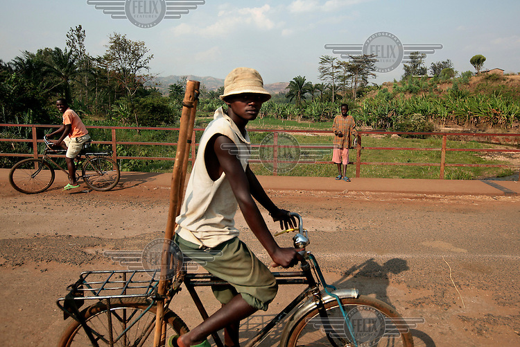 A man rides a bicycle on a bridge over the Kagunza River. /Felix Features
