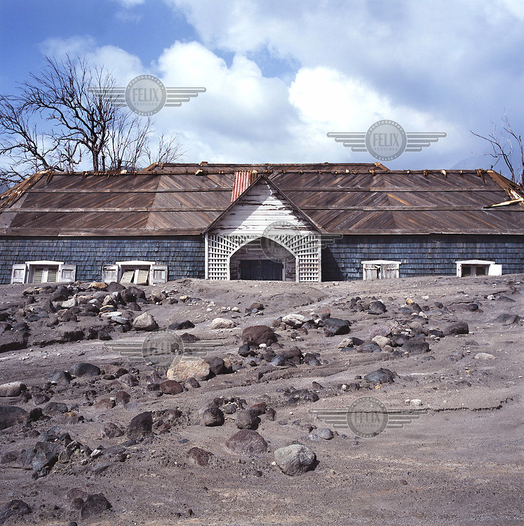 The roof of a destroyed building protrudes from the layers of rock, mud and ash from a pyroclastic flow which descended on the island's former capital in the volcanic eruption of 1995.  The Soufriere Hills volcano began erupting in July 1995, and remained active through the subsequent decade.  Up to 7,000 of the 10,500 inhabitants have been evacuated from the island, while other residents have been moved to the northernmost areas.  The southern region affected by the eruption is designated out of bounds to everyone except scientists.