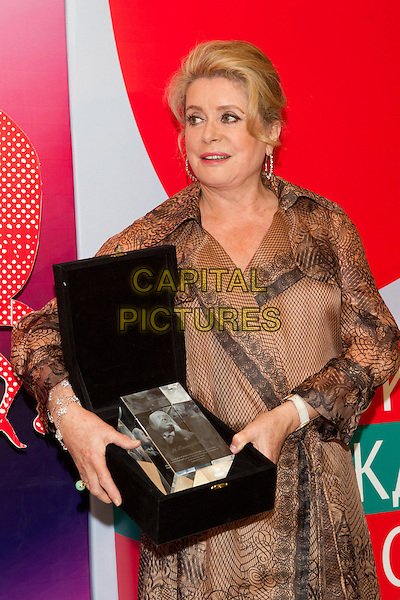 "Catherine Deneuve .Closing of the 34th MMKF. Deneuve won a prize I ""Trust"". Cinema ""October"", Moscow, Russia..June 30th, 2012.half length dress award trophy winner beige black print .CAP/PER/SB.©SB/PersonaStars/CapitalPictures"