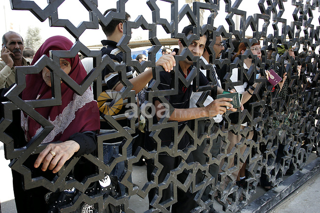 Palestinians stand behind the iron gate of the Rafah border waiting to cross the Rafah border crossing with Egypt, in the southern Gaza Strip on July 25, 2011. Photo by Abed Rahim Khatib