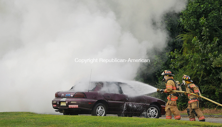 SEYMOUR, CT 18 AUGUST 2013--081813JS05-Firefighters douse a burning car during a mass casualty drill Sunday at Seymour High School. The scenario was a mass shooting inside the school with causalities. The drill was the first large scale, multi-jurisdictional drill the Town of Seymour has had in more than 30 years. The drill included local police, fire, emergency medical personnel as well as mutual aid responders from Beacon Falls, Oxford and Ansonia.   Jim Shannon Republican American