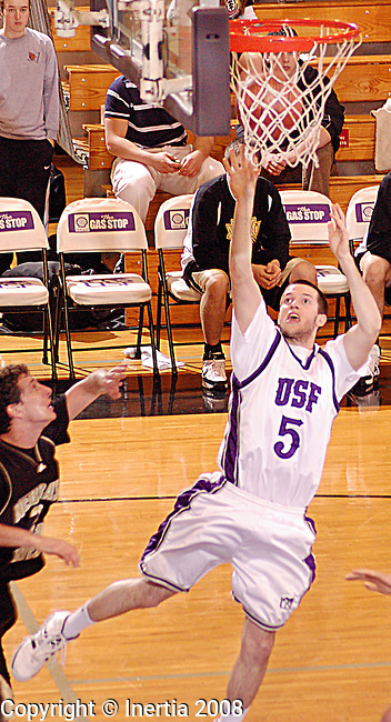 Sioux Falls, SD - February 16: Nick Selken #05 of University of Sioux Falls makes a layup after Marcus Minzel #20 of Nebraska failed to block Nick saterday afternoon at the Stewart Center. (photo by Heath Noess/Inertia)