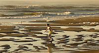 A woman walks across a tide pool along the beach in Amelia Island, FL