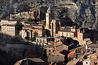 High angle view of Cathedral and Castle, Albarracin, Teruel, Spain, on February 13, 2006, pictured in the morning. The Cathedral, 1572-1600, was built by Martin de Castaneda, Pierres Vedel, and Alonso del Barrio de Ajo, in the Levantine Gothic style. At the top of the village is the 10th century Moorish castle, reached through cobbled streets of  houses constructed of wood and plaster with small windows. Albarracin, a beautiful village with National Monument status overlooking the Guadalivar River, lies 28 km from Teruel, in the National Park in the Montes Universales. It is on the border of three Spanish Kingdoms: Castille, Aragon and Valencia, has been occupied for hundreds of years and is known as the Eagles` Nest because it is built on a steep outcrop of rock surrounded by a deep gorge, a natural defence. Its buildings show  Moorish influence and even the name may derive from  the Berber clan Banu Razin who settled in the area during the 9th century. Picture by Manuel Cohen.