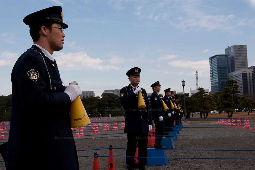 Japanese policemen using yellow plastic megaphones to control crowds at the entrance to the Imperial Palace on the occasion of Emperor Akihito's traditional birthday address at the Royal Palace, Tokyo, Japan. December 23rd 2008