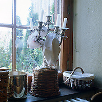 A silver candelabra on a wicker base with an antique cloth entwined around it sits on a window sill