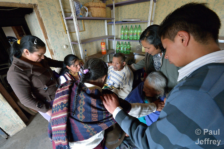 Visitors from the local Methodist Church pray with an elderly couple in their home in Romerillos, Ecuador.