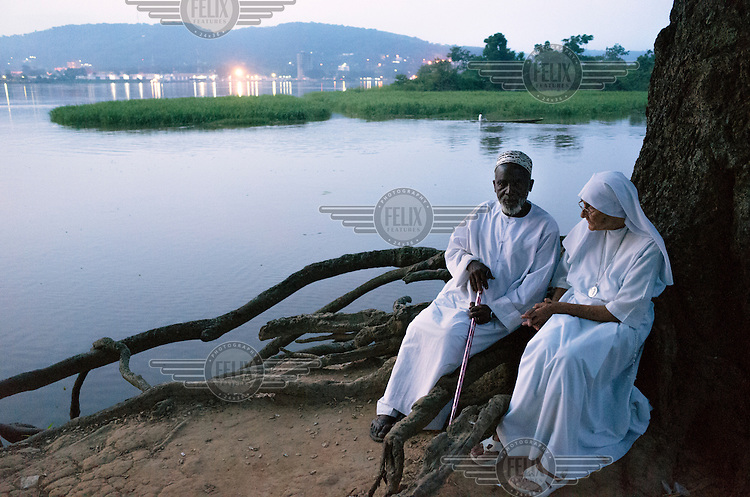 Imam Moussa Bawa, 72, and Sister Maria Concetta, 80, sit conversing on the banks of the Oubangi River. Across the river the lights of Bangui, the capital of the Central African Republic, can be seen. The Imam and the nun have known one another for many years. The sister, an experienced midwife, assisted during the birth of all eight of the imam's children. Conflict in CAR has caused more than a million people to flee their homes, one-quarter of them crossing an international border in their search for safety. Inter-communal violence between Christians and Muslims in CAR has further complicated the situation, for both those still inside the country, and for refugees abroad.<br /> The two religious leaders attempt to heal the wounds that have divided the Christian and Muslim communities in CAR. 'People come every day to my place to ask me for advice. I tell them that they have to forget the past. If someone harmed, you should not harm him, you should forgive,' says the imam.