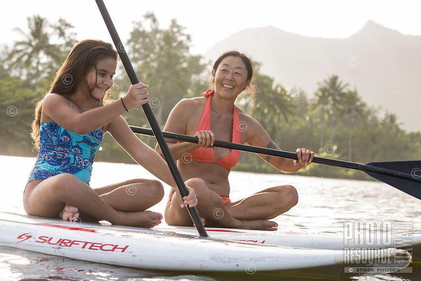 A family has fun during a standup paddling lesson on Wailua River, Kaua'i.
