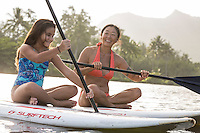 A family has fun during a standup paddling lesson on Wailua River, Kaua'i.