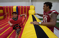 NWA Democrat-Gazette/J.T. WAMPLER Miller McDaniel, 8, of Bentonville gets encouraged by Kyrei Fisher (right) Saturday August 12, 2017 during the RazorbacksÕ annual Fan Day at the University of Arkansas. Football players and coaches were available for autographs with the soccer and volleyball teams.