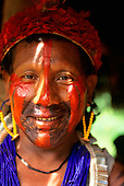 A-Ukre village, Brazil. Kayapo warrior with red urucum and black genipapo face paint, red feather headdress; Para State.
