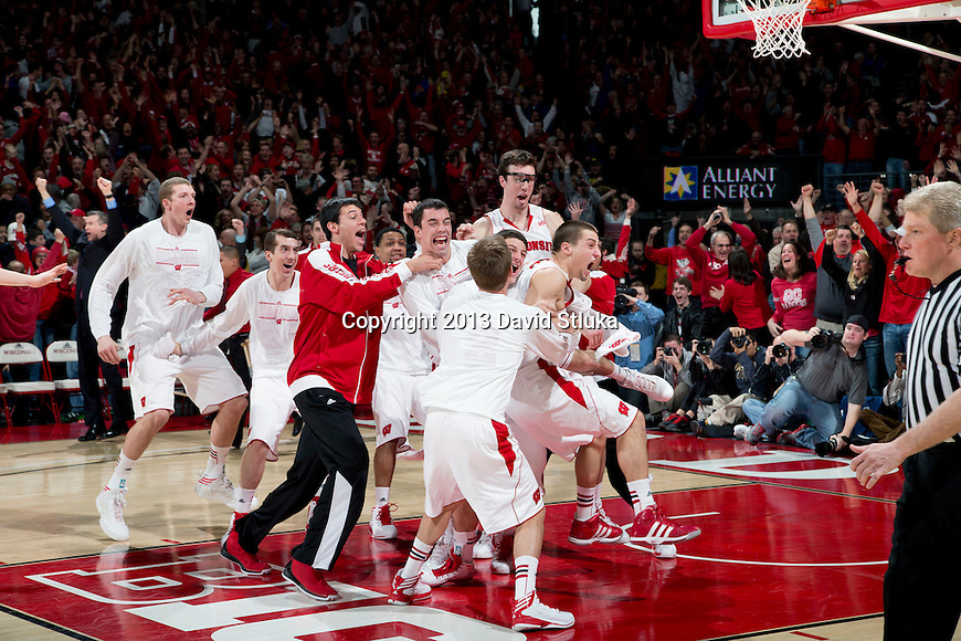 Wisconsin Badgers teammates celebrate Ben Brust (1) 3-pointer as time expires in regulation to tie the game during a Big Ten Conference NCAA college basketball game against the Michigan Wolverines Saturday, February 9, 2013, in Madison, Wis. The Badgers won 65-62 (OT). (Photo by David Stluka)