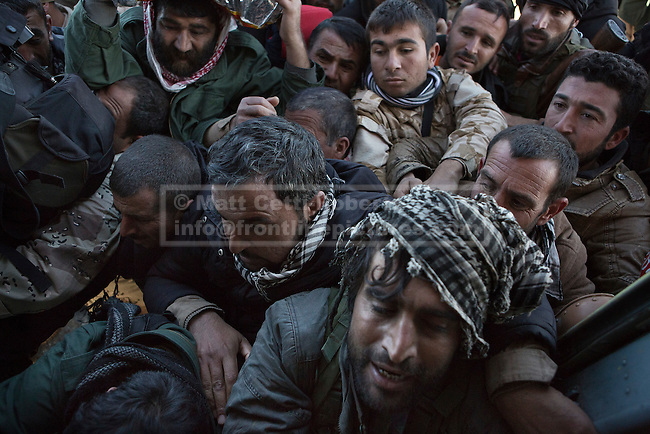 11/12/2014. Sinjar Mountains, Iraq. Yazidi fighters jostle to get a seat to escape from Mount Sinjar on an Iraqi Air Force Mi-171E Hip helicopter during a mission to resupply trapped Yazidi refugees.<br /> <br /> Although a well publicised exodus of Yazidi refugees took place from Mount Sinjar in August 2014 many still remain on top of the 75 km long ridge-line, with estimates varying from 2000-8000 people, after a corridor kept open by Syrian-Kurdish YPG fighters collapsed during an Islamic State offensive. The mountain is now surrounded on all sides with winter closing in, the only chance of escape or supply being by Iraqi Air Force helicopters.