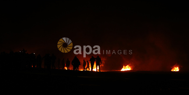 """Palestinian protesters calling themselves the """"night confusion units"""" burn tires as they gather near the Gaza-Israel border east of Jabalia in the northern Gaza Strip, February 11, 2019. In northern Gaza, a so-called """"confusion unit"""" also clashed with Israeli troops along the security fence, after approximately two months without such nighttime skirmishes. Photo by Dawoud Abo Alkas"""