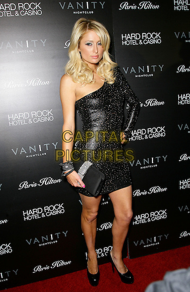 PARIS HILTON.Celebrates the Launch of ParisHilton.com at Vanity Nightclub inside the Hard Rock Hotel and Casino, Las Vegas, Nevada, USA, .16th January 2010..full length black one shoulder dress hand on hip ring studded studs clutch bag bracelets bangles platform shoes heels .CAP/ADM/MJT.©MJT/Admedia/Capital Pictures